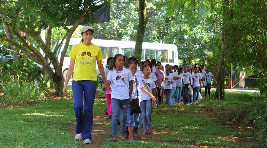 Young girls and camp counselor walk hand in hand