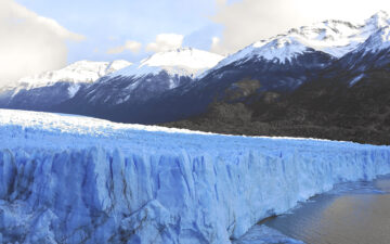 Large glacier melting under snow-capped mountain