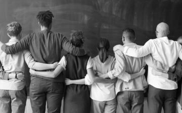 A black and white image of people standing with their arms around each other.